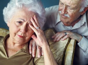 Elderly couple, woman holding her head with hand and man sitting with his hand on her shoulder consoling her.